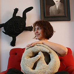 Mikaela Castledine in red chair with pangolin. Image courtesy of the artist