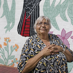 Printmaker Laurel Nannup stands in front of the mural she designed in Northbridge. Image: Christophe Canato